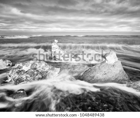Stock Photo Ice blocks lie on a black beach, the movement of the waves can be seen (long exposure), above a contrasting cloudy sky - Picture in black and white - Location: Iceland, Jökulsárlón (Jökulsarlon)
