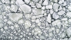 Ice blocks on the sea.  Cracked ice texture. Top view. Nature winter background.