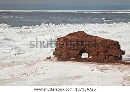 Ice breaking around an interesting product of erosion, a sandstone rock formation along the coast of Prince Edward Island, Canada.