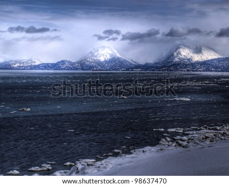 Ice breaking up in Mud bay near Homer Alaska in spring with the snowy Kenai Mountains in the background.
