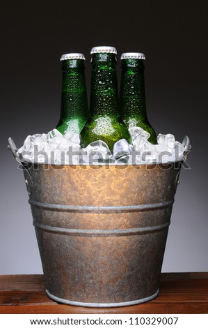 Ice bucket with three bottles of beer on a wet wood bar counter top. Vertical format on a light to dark gray background.