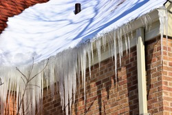 Ice build up in roof gutters creating a dam against drainage.