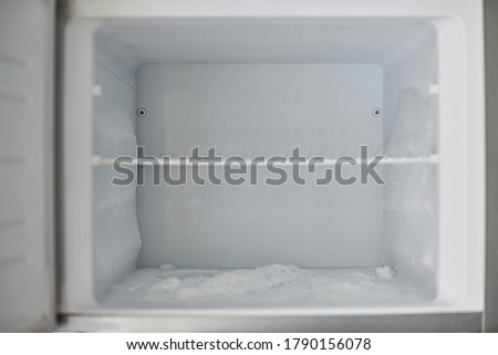 Ice buildup in freezer. Broken frozen refrigerator with built up ice and frost. Empty freezer drain is clogged. Photo stock ©