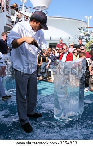 Ice carver sculpting a design in front of a crowd on a cruise liner