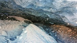 Ice cave in the snowy mountains. Tuyuk-Su glacier. Black ice reflects everything like a mirror. The ledge of stones collapsed. huge cracks in the ice tunnel. Snowy mountains of Almaty, Kazakhstan.
