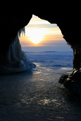 Ice cave with icicles framing sunset over Lake Superior on Apostle Islands, Wisconsin
