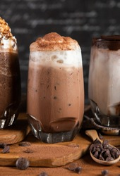 Ice chocolate, toppings by floating foam milk and burned sugar in a tall of clear glass on dark gray real wood and chopping board. Decorated with choc chip. Popular drink to quench thirst to cool down