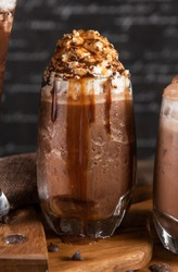Ice chocolate, toppings by floating foam milk and Choco lava in a tall of clear glass on dark gray real wood and chopping board. Decorated with choc chip. Popular drink to quench thirst to cool down