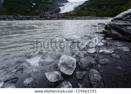 Ice chunks cover beach like boulders and pebbles on river near end of glacier in Alaska