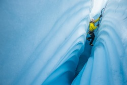 Ice climber lowered into narrow ice canyon on the Matanuska Glacier. He climbs between walls of strange wavy patterns in the ice carved by a river of melt water.