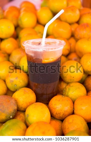 Ice coffee brew mix with orange juice on pile orange #1036287901
