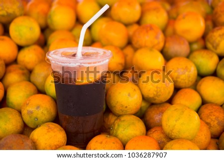 Ice coffee brew mix with orange juice on pile orange #1036287907