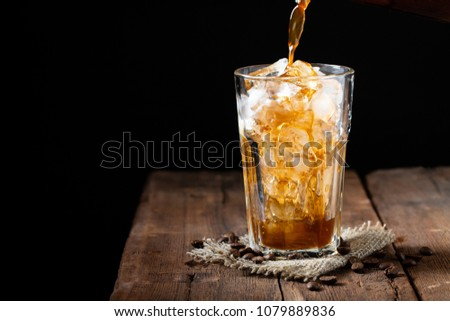 Ice coffee in a tall glass over and coffee beans on a old rustic wooden table. Cold summer drink on a dark background with copy space. The process of pouring drink from a coffee pot into a glass #1079889836