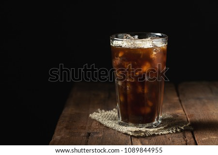 Ice coffee in a tall glass over and coffee beans on a old rustic wooden table. Cold summer drink on a dark background with copy space