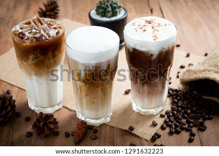 Ice coffee in a tall glass with coffee beans on the table. Latte, Cappuccino and Mocha. #1291632223