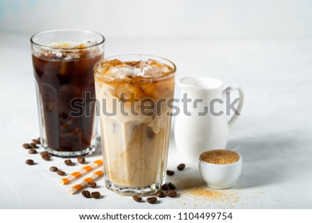 Ice coffee in a tall glass with cream poured over and coffee beans. Cold summer drink on a light blue background.