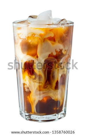 Ice coffee in a tall glass with cream poured over and coffee beans. Cold summer drink on a light background.