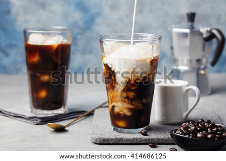 Ice coffee in a tall glass with cream poured over and coffee beans on a grey stone background