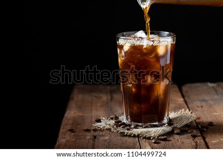 Ice coffee in a tall glass with cream poured over and coffee beans on a old rustic wooden table. Cold summer drink on a dark wooden background with copy space.