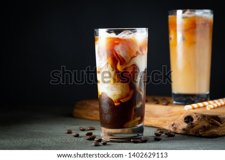 Ice coffee in a tall glass with cream poured over, ice cubes and beans on a old rustic wooden table. Cold summer drink with tubes on a black background with copy space. #1402629113
