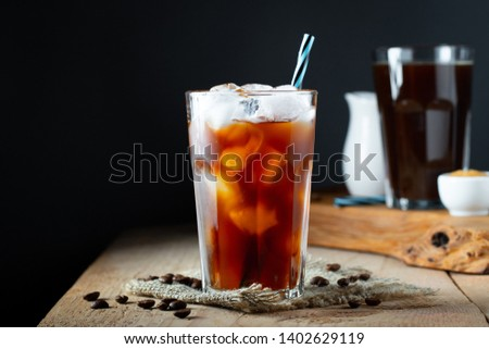 Ice coffee in a tall glass with cream poured over, ice cubes and beans on a old rustic wooden table. Cold summer drink with tubes on a black background with copy space. #1402629119