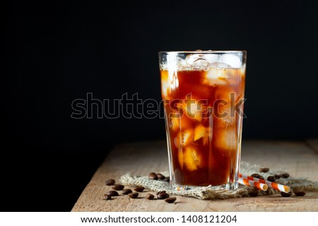 Ice coffee in a tall glass with cream poured over, ice cubes and beans on a old rustic wooden table. Cold summer drink with tubes on a black background with copy space #1408121204