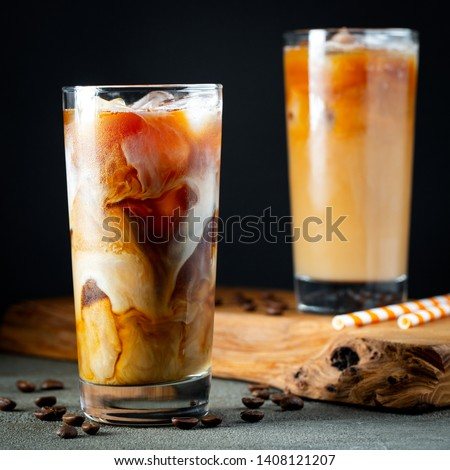 Ice coffee in a tall glass with cream poured over, ice cubes and beans on a old rustic wooden table. Cold summer drink with tubes on a black background #1408121207