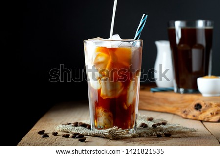 Ice coffee in a tall glass with cream poured over, ice cubes and beans on a old rustic wooden table. Cold summer drink with tubes on a black background with copy space #1421821535