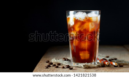 Ice coffee in a tall glass with cream poured over, ice cubes and beans on a old rustic wooden table. Cold summer drink with tubes on a black background with copy space #1421821538
