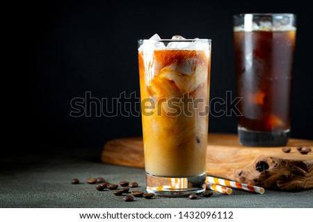 Ice coffee in a tall glass with cream poured over, ice cubes and beans on a old rustic wooden table. Cold summer drink with tubes on a black background with copy space #1432096112