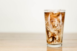 Ice coffee on a wood table with cream being poured into it showing the texture and refreshing look of the drink, with a clean background.