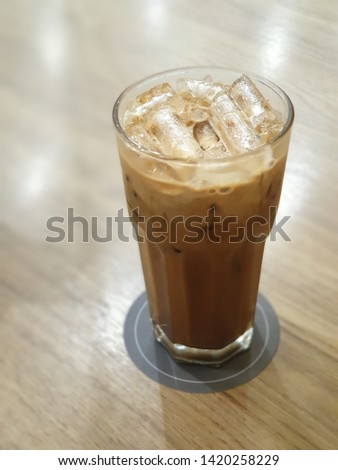 Ice coffee on a wooden table.   Cold coffee to drink during hot weather and help quench thirst. #1420258229