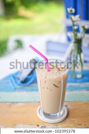 ice coffee on grunge wood table in garden