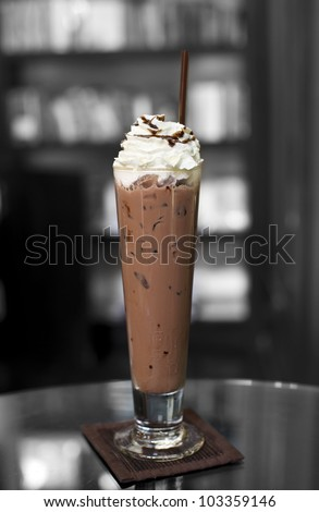 Ice coffee on top with whip cream and chocolate caramel with bookshelf background