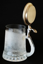 Ice cold beer mug with pewter lid ready to be filled with beverage on dark background.