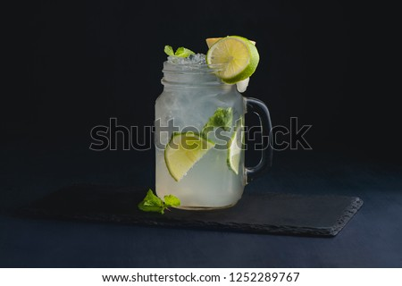Ice cold classic lime lemonade in a vintage glass mason jar. Dark background with copy space for a menu.