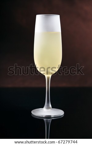 Ice cold frosted glass of champagne on black reflective table with ...