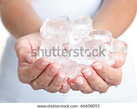 Ice cold hands. Woman hands holding ice cubes - closeup.