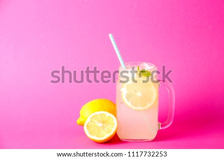 Ice cold lavander lemonade, lemon, straw, mint. Classic virgin mojito cocktail, non alcoholic drink with ice in vintage mason jar glass, bright pink isolated background. Copy space, top view close up.
