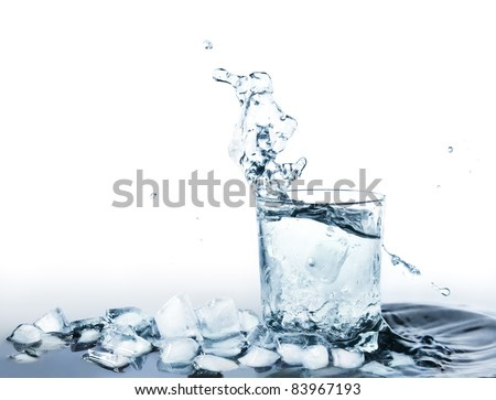 Ice cold water drink in a glass standing in water with ice cubes and water splashing