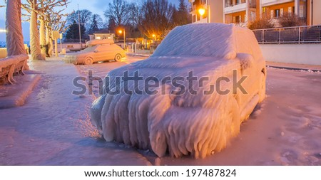 Ice covered car by Lake Geneva at the town of Versoix, Geneva, Switzerland in a winter morning.