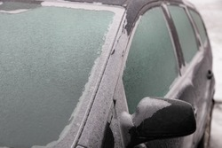 Ice-covered car side mirror, glass, windscreen and side doors, close up front side view of an icy vehicle on a winter day after freezing rain in Russia