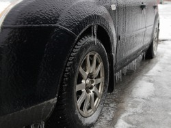 Ice-covered car side view in perspective, wheel and icicles on threshold, icy vehicle on a winter day after freezing rain