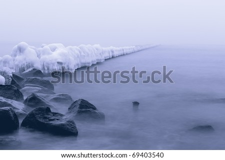 Ice-covered coastal protection during the winter fog. shot at long exposures.