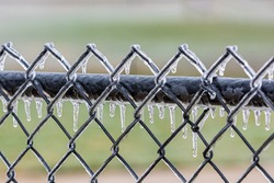 Ice covered fence after winter ice storm. Concept of winter weather and freezing rain.