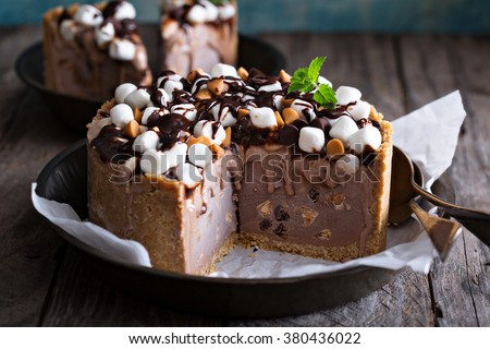 Ice cream cake with marshmallows and peanuts topped with chocolate syrup