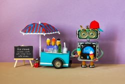 Ice cream cart. The robot seller is holding waffle cones with apple and strawberry ice cream. Big blue red umbrella, black chalkboard easel menu on sandy purple beach background