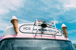 Ice cream cone with a pink ice cream truck or van in the background.