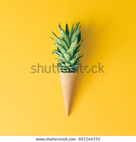 Shutterstock Ice cream cone with pineapple leaves on bright yellow background. Fruit and candy concept. Flat lay.