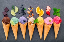 ice cream flavor in cones blueberry ,lime ,pistachio ,almond ,orange ,chocolate ,vanilla and coffee set up on dark stone background . Summer and Sweet menu concept.